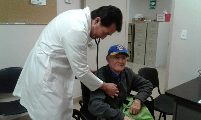 Adulto mayor atendido por un médico